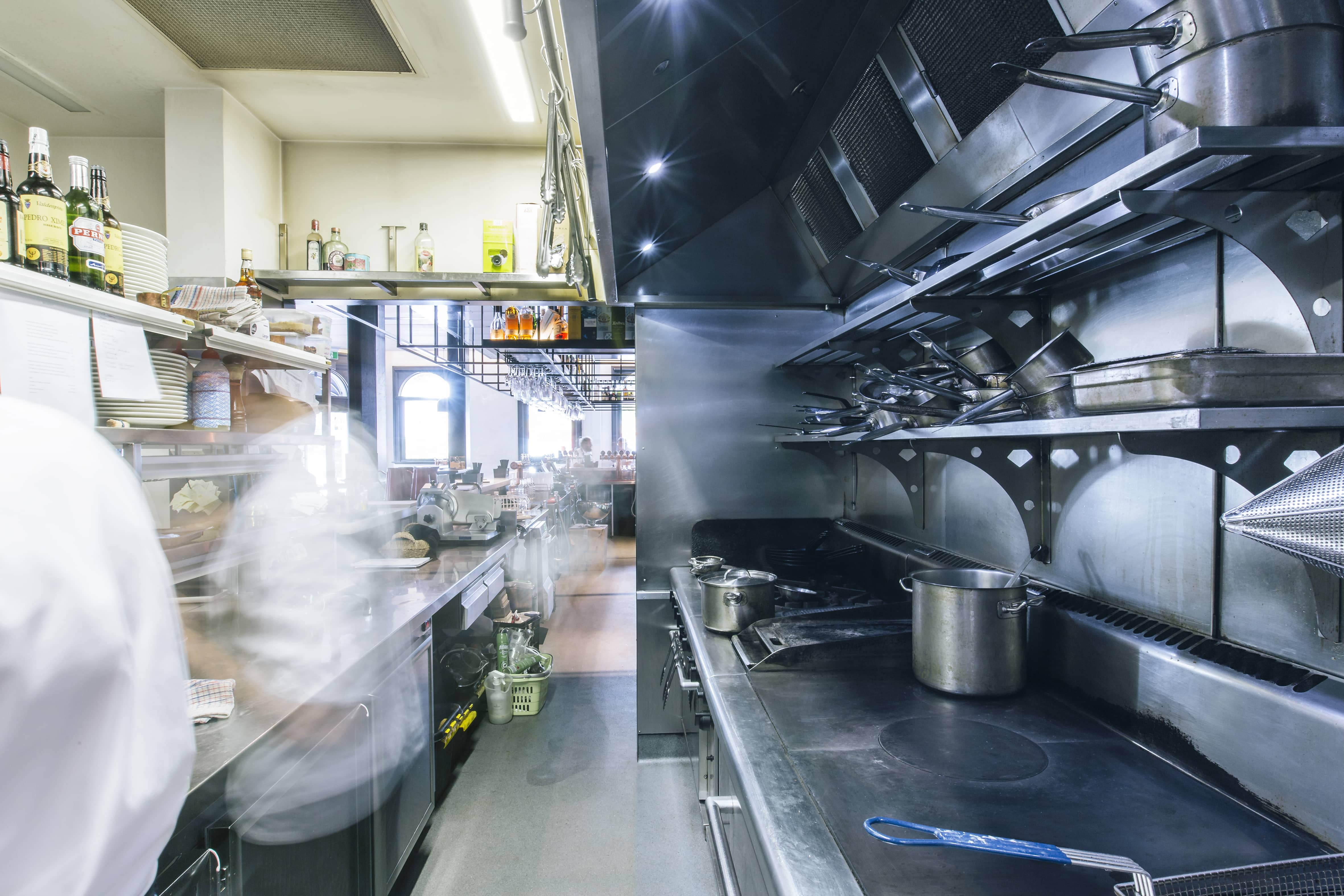 Commercial restaurant kitchen with stove tops & chefs